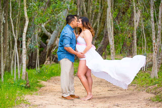 Couple kissing during a maternity photoshoot
