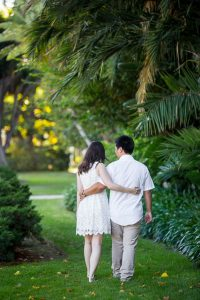 Engaged couple walking together around the Santa Barbara Courthouse grounds.