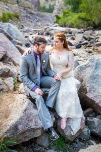 Bride and groom sitting on rocks in the Colorado Rockies.