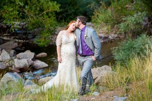 Bride and groom posing with the Rockie Mountains behind them.