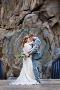 Newlyweds embracing on a bridge on a Boulder, Colorado trail in the Rockies mountains.