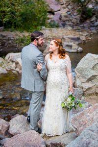 Bride and groom embracing on boulders in Boulder, Colorado.