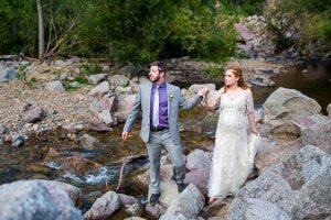 Newlyweds walking on boulders in Boulder, Colorado.