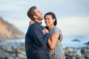 Bride and groom laughing together during their engagement photos at Hendry's Beach in Santa Barbara.