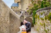 Wedding photographs of couple walking together in the Cité de Carcassonne, a medieval fortress.