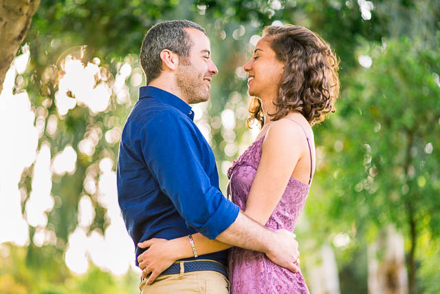 The newly engaged couple laughing together at their Tel Aviv engagement photoshoot.