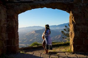 Expectant mother smiles for the camera during her maternity boudoir photoshoot at Knapp's Castle in Santa Barbara.