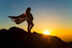 Maternity boudoir silhouette photos on top of a rock in Santa Barbara.