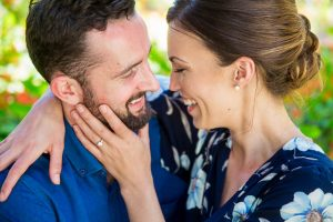 Engaged couple laughing together at the Goleta Butterfly Grove.