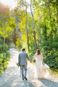 Newlyweds walking on a trail in Boulder, Colorado, while holding hands.