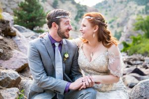 Bride and groom sitting on rocks in the Colorado Rockies.