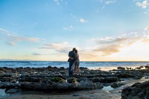 The newly engaged couple at Hendry's Beach rocks.