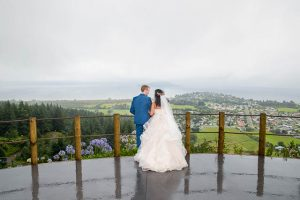 Bride and groom looking over the view from the Skyline Rotorua wedding venue.