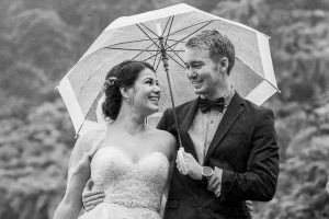 Bride and groom using a clear umbrella to shield them from the rain during their Blue Lake Rotorua New Zealand wedding Day After photos.