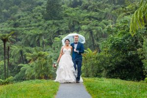 Bride and groom using a clear umbrella to shield them from the rain during their Green Lake wedding photos in Rotorua, New Zealand.