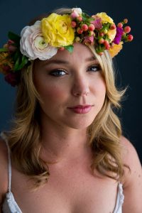Feminine portrait of a woman with a flower crown at her Los Angeles boudoir photoshoot.