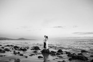 A bride and groom strolling along the beach in Santa Barbara during their engagement photo session.