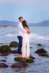 A couple snuggling together on the beach in Santa Barbara at Sunset during their engagement photo session.