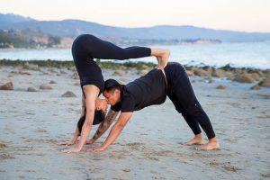 The engaged couple doing yoga poses during their yogi engagement photoshoot.