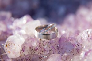 Wedding rings placed on amethyst rock formation.