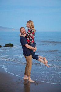 Couple having fun, being playful at their Santa Barbara beach engagement photoshoot.