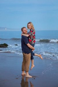 Couple having fun, being playful at their Santa Barbara beach engagement photoshoot.