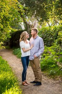 Couple embracing by the flowers during their Santa Barbara engagement photoshoot.
