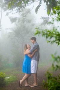 Engaged couple taking photos at their engagement photoshoot in Monteverde, Costa Rica, as the clouds roll in.