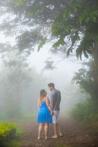 Engaged couple taking photos at their engagement photo session in Monteverde, Costa Rica, as the clouds roll in.