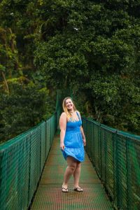 Woman twirling in her dress on a hanging bride in the Costa Rican rain cloud forest.
