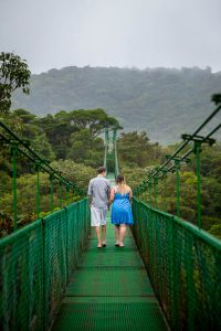 Engaged couple walking across the Selvatura Park Monteverde cloud forest in Costa Rica during their adventurous engagement session.
